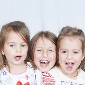 Three young girls with missing teeth smiling