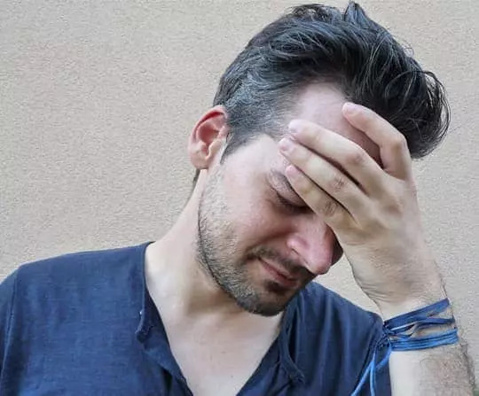 Man holding head from TMJ pain